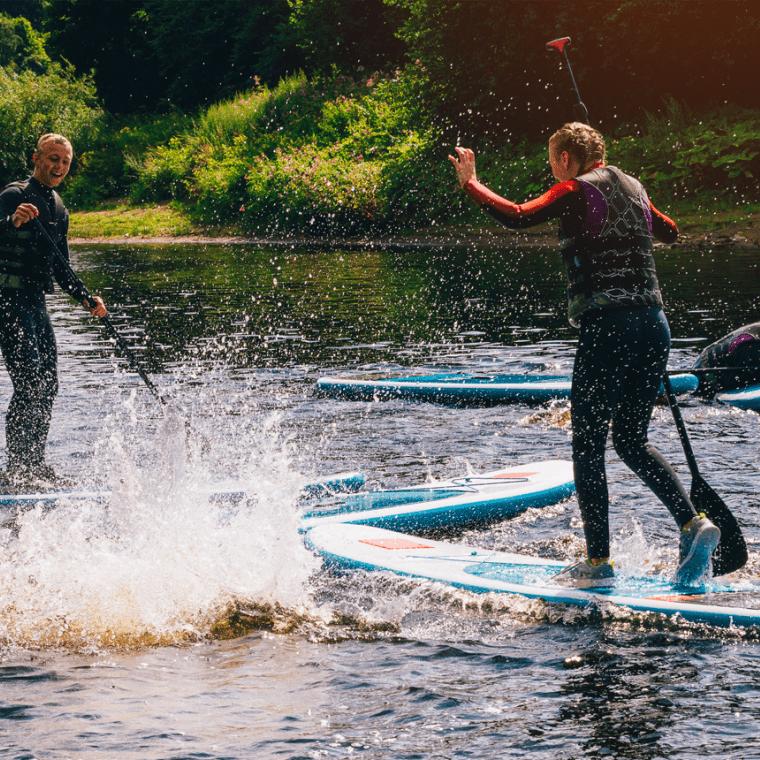 Des ados font du paddle au lac du lambon